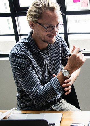 mężczyzna z zegarkiem podczas pracy biurowej