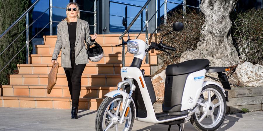 Femme quittant un bâtiment et se dirigeant vers une moto Cooltra en stationnement