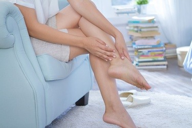 woman touching her legs sitting on sofa