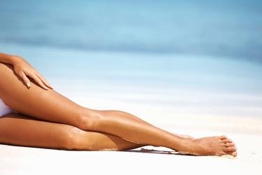 woman tanning legs on a beach