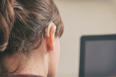kobieta z aparatem słuchowym ogląda wideo z transkrypcją