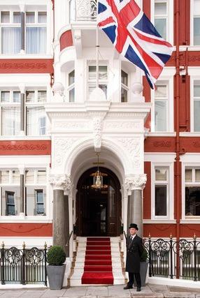 Concierge steht vor einem roten Hotel mit hängender Englandflagge