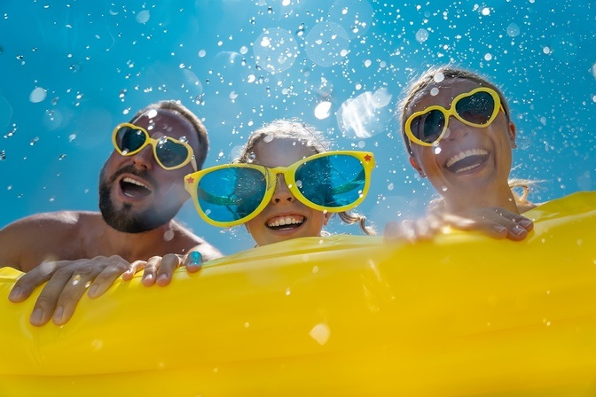 Family having fun at the pool with big yellow sunglasses on